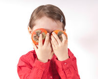 Persimmons Eyes. Pre-schooler girl holding two persimmons to her eyes royalty free stock photography