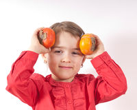 Persimmons Girl. Pre-schooler girl holding two persimmons to her head royalty free stock images