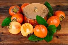 Persimmons kaki owoc skład na starym drewnie Orientalny wschodu wciąż życie Obrazy Royalty Free