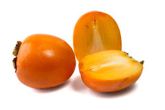 Persimmons, one whole and one cut in two pieces. On a white background Royalty Free Stock Image