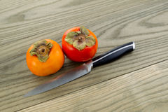 Persimmons with Paring Knife on aged white ash wood Stock Image