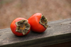 Persimmons on rail Stock Photography