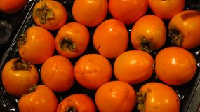 Persimmons in Supermarket. Crate filled with persimmons sold in a supermarket Royalty Free Stock Images