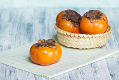 Persimmons on the table Stock Images