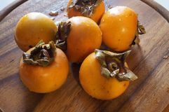 Persimmons on the table Royalty Free Stock Photos