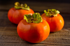 Persimmons Three on a Plank. Three persimmons on a rustic wooden plank, fall fruit, close-up Stock Photography