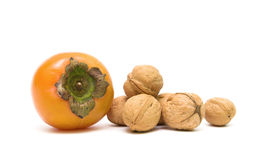 Persimmons and walnuts isolated on white background Stock Photos