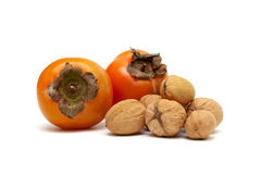 Persimmons and walnuts  on white background Stock Image