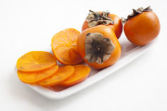 Persimmons on white plate Royalty Free Stock Photography