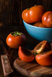 Persimmons on Wooden Background. Sliced Persimmon for Three with Knife and Some Fruits in Blue Bowl on Background. Vertical Royalty Free Stock Image