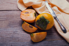 Persimmons on the wooden table close-up. Royalty Free Stock Photos