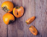 Persimmons on the wooden table, top view. Stock Image