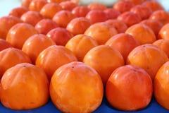 Persimon frutifica teste padrão na fruta do arranjo das fileiras Imagem de Stock