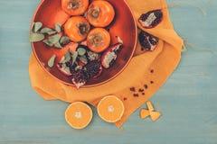 Persimoner med klippta apelsiner och granatäpplen på plattan på orange bordduk Royaltyfria Bilder