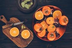 Persimoner med klippta apelsiner och granatäpplen på plattor och träbräde Royaltyfria Foton