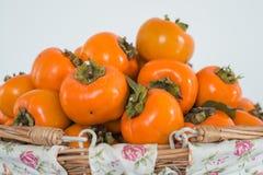 Persimonfrukt i korgen Arkivfoton