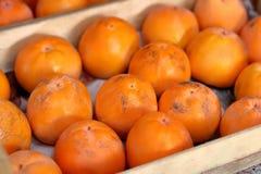Persimonfrukt i träasken royaltyfri foto