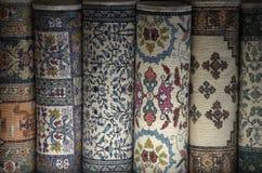 Persiska mattor vikta i rullar i Tunisien Arkivbilder