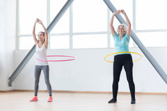 Persistent positive women exercising with hula hoops. Making your waist thinner. Good looking energetic sporty women holding their hands up and smiling while Royalty Free Stock Image