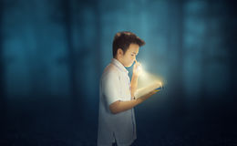 Persistent Reading in the dark with flashlight. A young boy wearing school uniform reading a book in the dark forest while holding a flashlight Royalty Free Stock Image