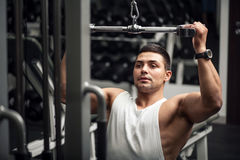 Persistent serious man training in a gym. Physical strength. Hard working persistent man holding his hand up and pushing the weight while using a gym apparatus Royalty Free Stock Photos