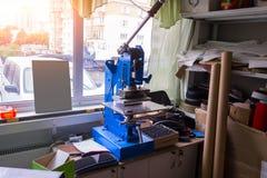 Persmachine in de workshop voor het doen van het in reliëf gemaakt embleem en le stock foto
