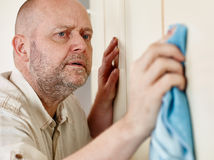 Persnickety male. Homeworks, persnickety male cleans the cupboard doors royalty free stock photo