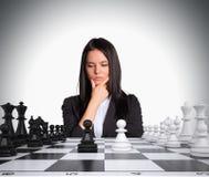 Perso nella donna di pensiero che esamina scacchiera Immagini Stock
