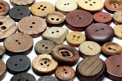 Perso nella folla - quantità di bottoni di legno d'annata su fondo bianco Fotografia Stock