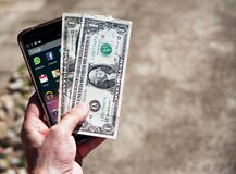Persom Holding Black Android Smartphone and 2 1 U.s. Dollar Stock Photo