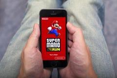 Person übergibt das Halten von iPhone mit Super-Mario Run-Spiel-APP stockbilder