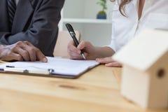 Person& x27; сочинительство ручки шариковой авторучки владением руки s на договоре подряда p Стоковая Фотография