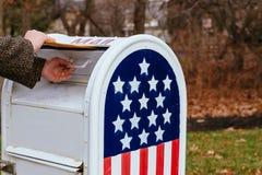 Person& x27特写镜头; 投入信件邮箱美国国旗的s手 库存照片