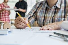 Person& x27特写镜头; s递在方案的图画计划与archit 免版税库存照片