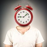 Person with an alarm clock in place of the head stock photos