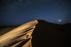 Person alone under night sky in the desert stock photography