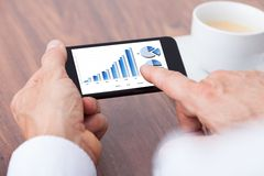 Person analyzing graph on mobile. Close-up Of A Businessman Analyzing Graph On Smartphone Royalty Free Stock Image