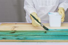 A person applies  dye to the wood. A person applies blue dye to the wood with a brush Royalty Free Stock Images