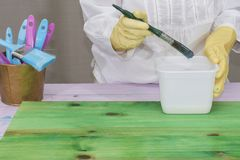 A person applies varnish to wood. A person applies a colorless varnish to a green wood with a brush Stock Photos