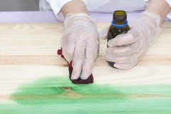 A person applies  dye to the wood. A person applies green dye to the wood with a rag Stock Photos
