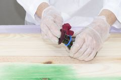 A person applies  dye to the wood. A person applies green dye to the wood with a rag Stock Photo