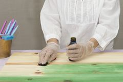A person applies  dye to the wood. A person applies green dye to the wood with a rag Royalty Free Stock Photo