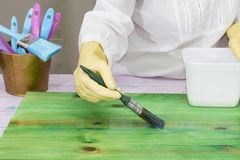 A person applies varnish to wood. A person applies a colorless varnish to a green wood with a brush Royalty Free Stock Photography