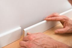 Person applying skirting on wall Royalty Free Stock Image