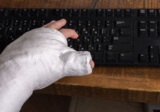 Person with arm cast typing on a keyboard Stock Photos