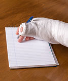 Person with an arm cast writing a note Royalty Free Stock Photography