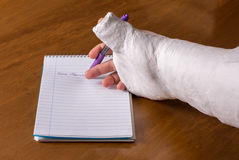 Person with an arm cast writing a note Royalty Free Stock Photo
