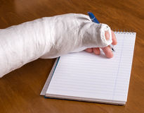 Person with an arm cast writing a note Royalty Free Stock Images