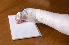 Person with an arm cast writing a note Royalty Free Stock Image