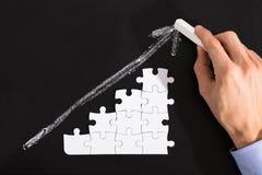 Person Arranging Puzzles On Blackboard photographie stock libre de droits